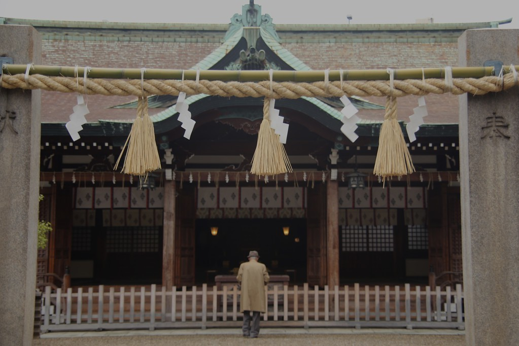 An elderly man worships at Imamiya Ebisu Shrine