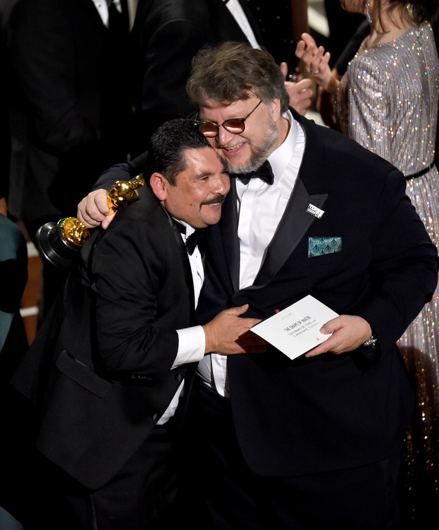 ". Guillermo del Toro, right, winner of the award for best picture for ""The Shape of Water\"" celebrates with Guillermo Rodriguez from \""Jimmy Kimmel Live!\"" at the Oscars on Sunday, March 4, 2018, at the Dolby Theatre in Los Angeles. (Photo by Chris Pizzello/Invision/AP)"