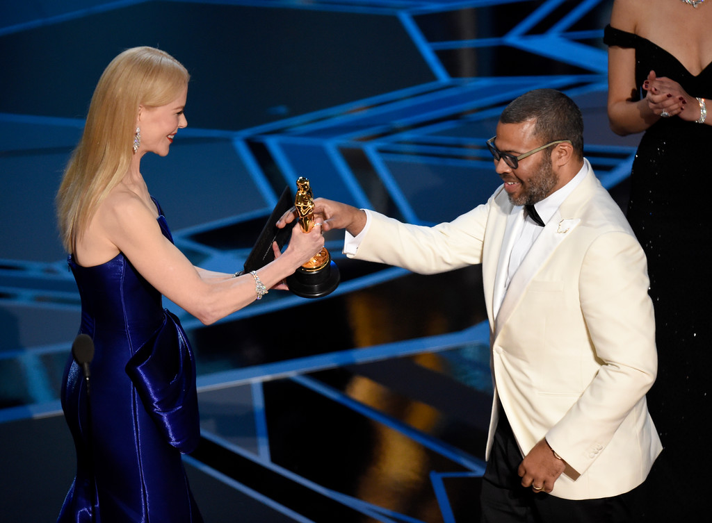 ". Nicole Kidman, left, presents Jordan Peele with the award for best original screenplay for ""Get Out\"" at the Oscars on Sunday, March 4, 2018, at the Dolby Theatre in Los Angeles. (Photo by Chris Pizzello/Invision/AP)"