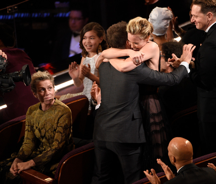 ". Sam Rockwell, center, winner of the award for best performance by an actor in a supporting role for ""Three Billboards Outside Ebbing, Missouri\"" hugs Leslie Bibb, right, as Frances McDormand, left, looks on at the Oscars on Sunday, March 4, 2018, at the Dolby Theatre in Los Angeles. (Photo by Chris Pizzello/Invision/AP)"