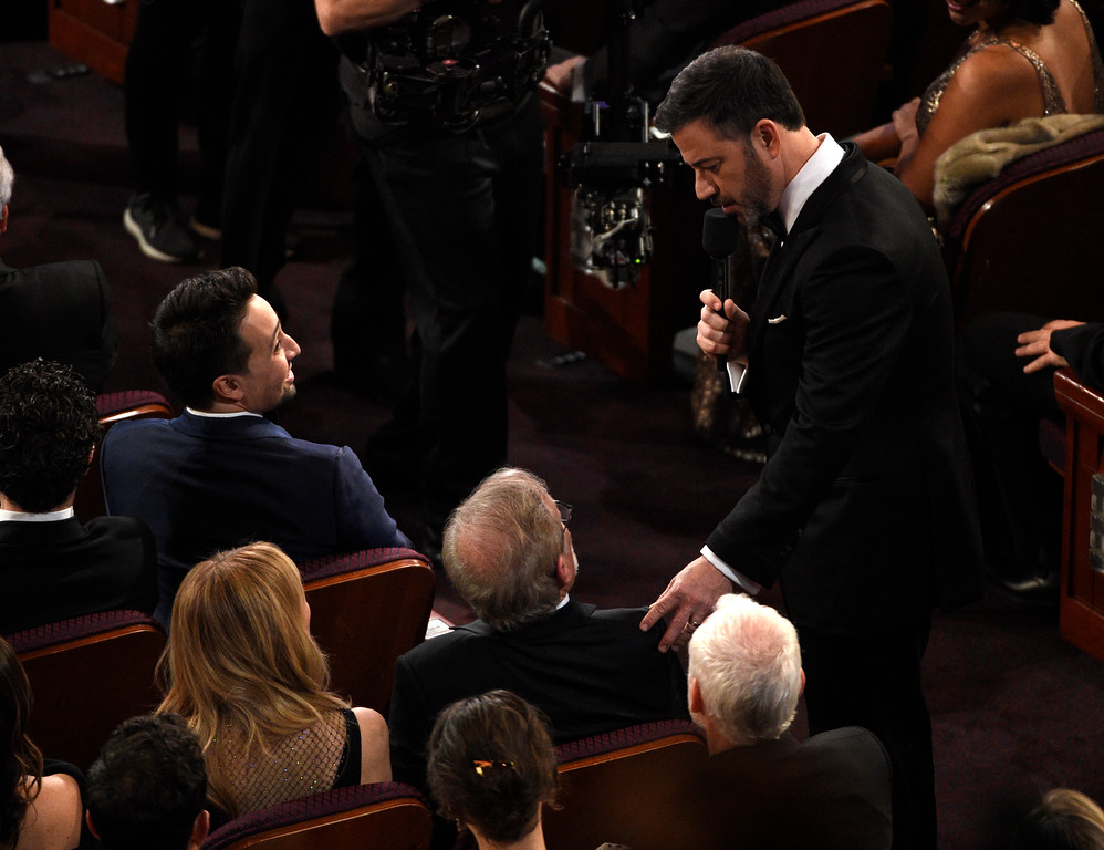 . Host Jimmy Kimmel talks with Steven Spielberg in the audience as Lin-Manuel Miranda, top left, looks on, at the Oscars on Sunday, March 4, 2018, at the Dolby Theatre in Los Angeles. (Photo by Chris Pizzello/Invision/AP)