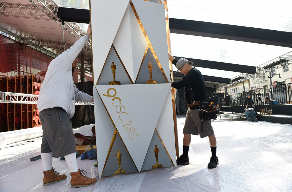 . Crew members Robert Kolody, left, and Manny Alcaraz put up a backdrop near the arrivals area before the rollout of the red carpet for Sunday\'s 90th Academy Awards in front of the Dolby Theatre on Wednesday, Feb. 28, 2018, in Los Angeles. (Photo by Chris Pizzello/Invision/AP)