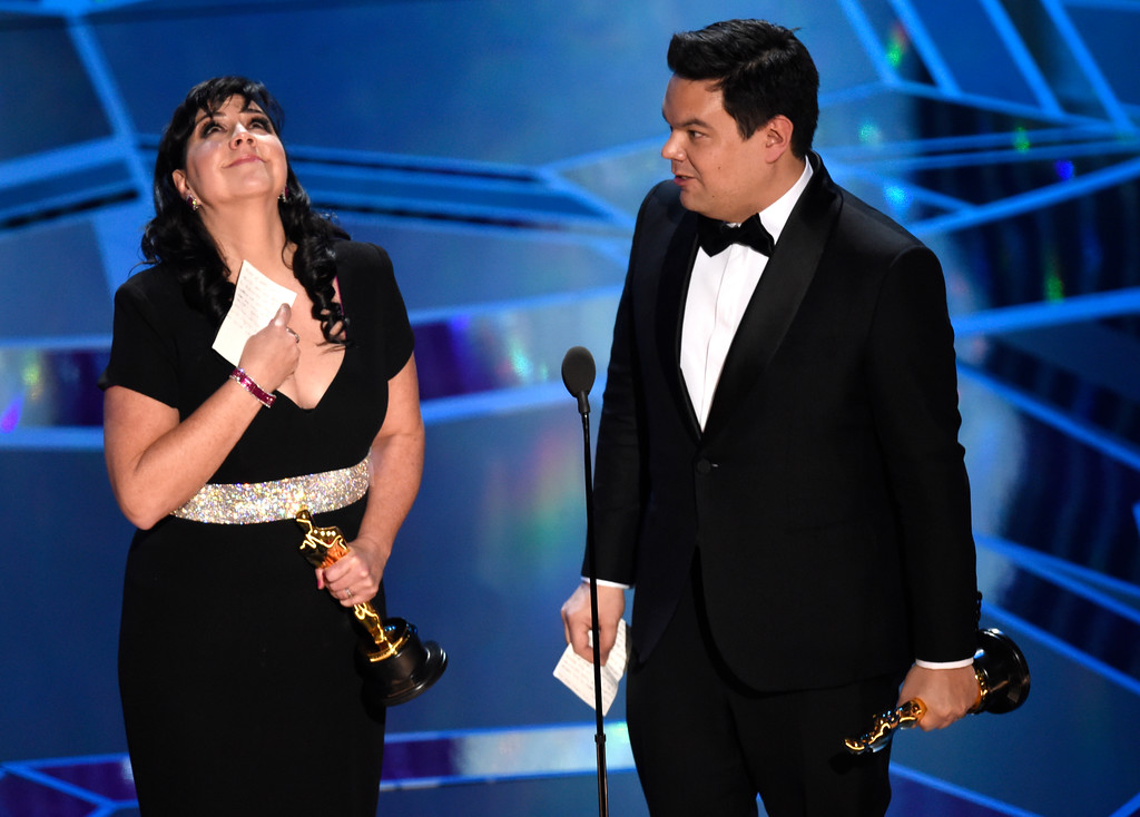 ". Kristen Anderson-Lopez, left, and Robert Lopez accept the award for best original song for ""Remember Me\"" from \""Coco\"" at the Oscars on Sunday, March 4, 2018, at the Dolby Theatre in Los Angeles. (Photo by Chris Pizzello/Invision/AP)"