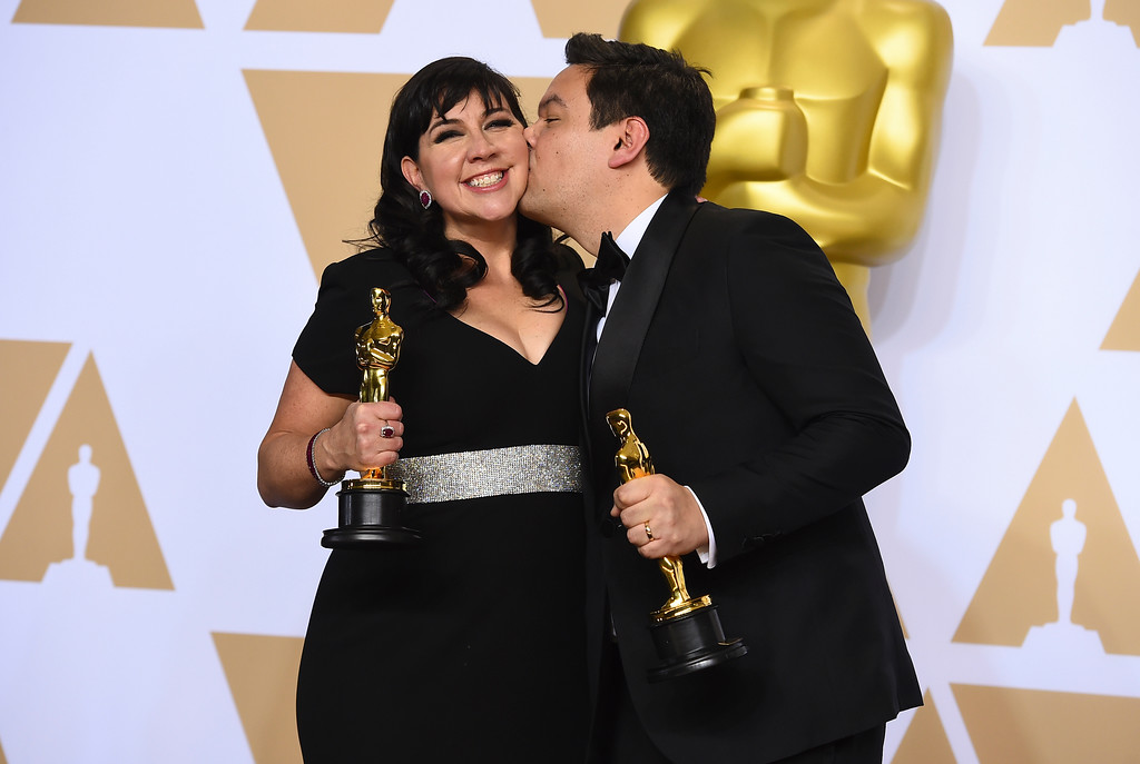 ". Kristen Anderson-Lopez, left, and Robert Lopez, winners of the award for best original song for ""Remember Me\"" from \""Coco\"", pose in the press room at the Oscars on Sunday, March 4, 2018, at the Dolby Theatre in Los Angeles. (Photo by Jordan Strauss/Invision/AP)"