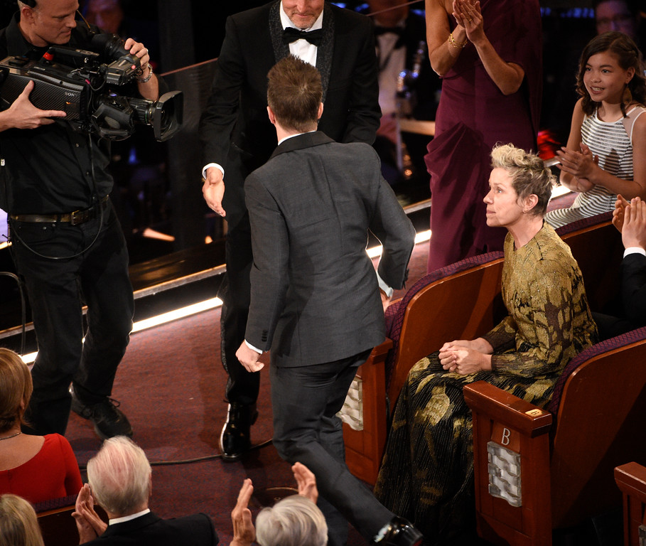 ". Sam Rockwell, winner of the award for best performance by an actor in a supporting role for ""Three Billboards Outside Ebbing, Missouri\"" walks to the stage as Frances McDormand looks on at the Oscars on Sunday, March 4, 2018, at the Dolby Theatre in Los Angeles. (Photo by Chris Pizzello/Invision/AP)"