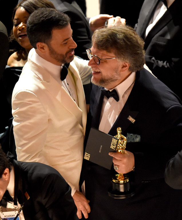 ". Jimmy Kimmel, left, congratulates Guillermo del Toro in the audience after winning the award for best picture for ""The Shape of Water\"" at the Oscars on Sunday, March 4, 2018, at the Dolby Theatre in Los Angeles. (Photo by Chris Pizzello/Invision/AP)"