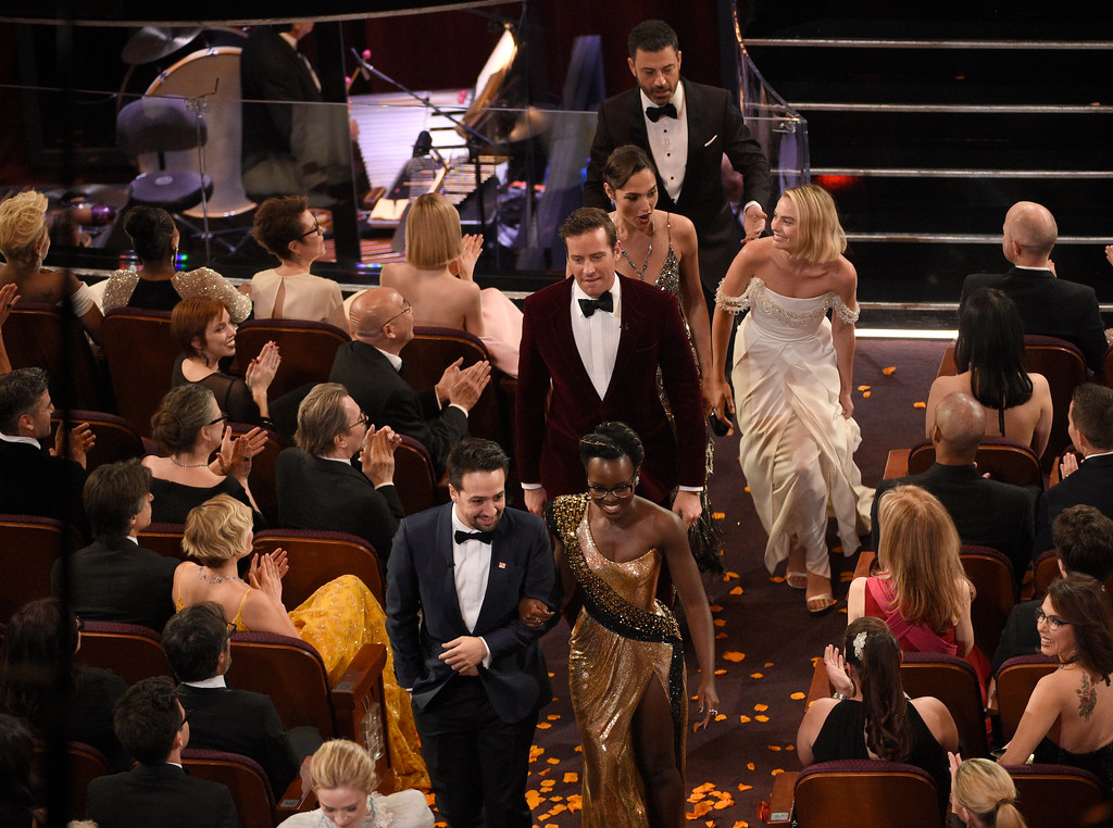 . Lin-Manuel Miranda, from left, Lupita Nyong\'o lead other celebrities out of the Dolby Theatre at the Oscars on Sunday, March 4, 2018, in Los Angeles. The group visited a movie theater across the street to surprise movie-goers. (Photo by Chris Pizzello/Invision/AP)