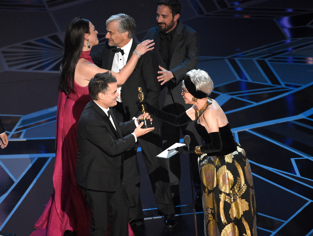 ". Rita Moreno, right, presents Sebastian Lelio, foreground center, and from background left, Daniela Vega, Francisco Reyes, and Pablo Larrain with the award for best foreign language film for ""A Fantastic Woman\"" at the Oscars on Sunday, March 4, 2018, at the Dolby Theatre in Los Angeles. (Photo by Chris Pizzello/Invision/AP)"
