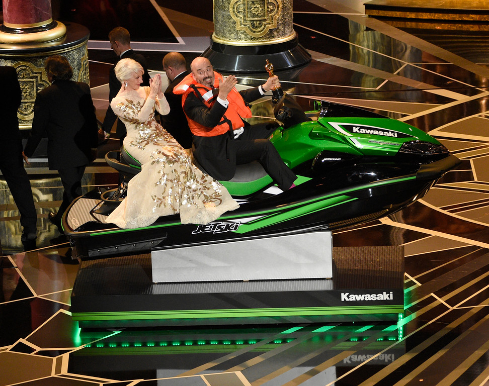 ". Helen Mirren, left, accompanies Mark Bridges, winner for the award for best costume design for ""Phantom Thread,\"" as he wins a jet ski for having the shortest acceptance speech at the Oscars on Sunday, March 4, 2018, at the Dolby Theatre in Los Angeles. (Photo by Chris Pizzello/Invision/AP)"