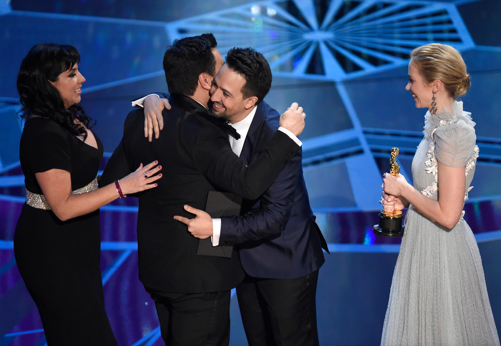 ". Emily Blunt, from right, and Lin-Manuel Miranda present Robert Lopez and Kristen Anderson-Lopez the award for best original song for ""Remember Me\"" from \""Coco\"" at the Oscars on Sunday, March 4, 2018, at the Dolby Theatre in Los Angeles. (Photo by Chris Pizzello/Invision/AP)"