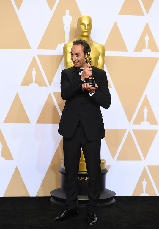 ". Alexandre Desplat, winner of the award for best original score for ""The Shape of Water\"", poses in the press room at the Oscars on Sunday, March 4, 2018, at the Dolby Theatre in Los Angeles. (Photo by Jordan Strauss/Invision/AP)"