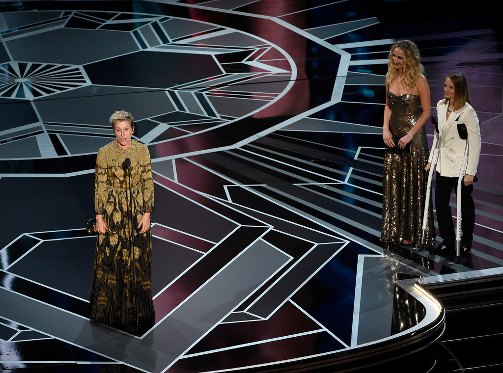 ". Frances McDormand accepts the award for best performance by an actress in a leading role for ""Three Billboards Outside Ebbing, Missouri\"" as Jennifer Lawrence and Jodie Foster look on from right at the Oscars on Sunday, March 4, 2018, at the Dolby Theatre in Los Angeles. (Photo by Chris Pizzello/Invision/AP)"