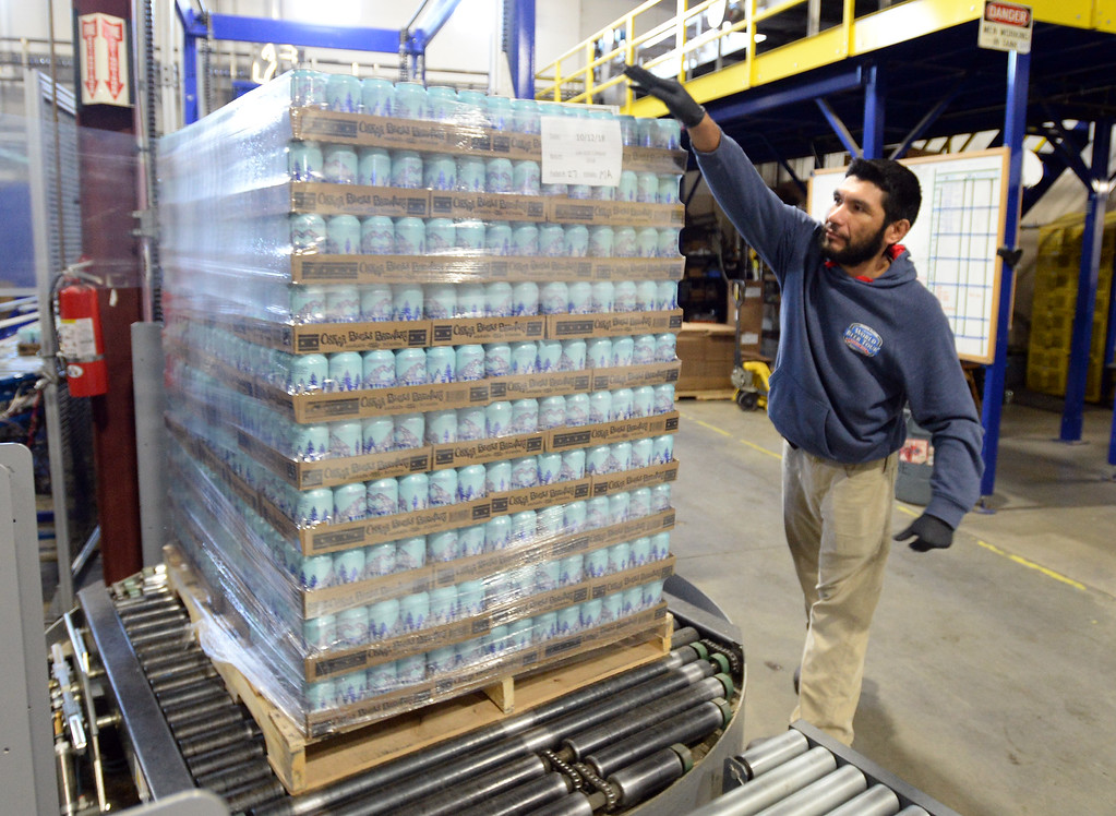 . LONGMONT, CO - October 12, 2018: Manny Arellano labels a cube of water cans heading to Florida. Thousands of units of water are being canned at Oskar Blues in Longmont on Friday for Hurricane Michael relief. The Can\'d Aid Foundation has partnered with Oskar Blues Brewery and Ball Corporation  to provide canned water for disaster relief.   (Photo by Cliff Grassmick/Staff Photographer)