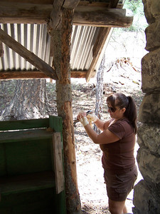 Anna Flores scraping bark from a post at the Pack Rat Unit Kitchen.