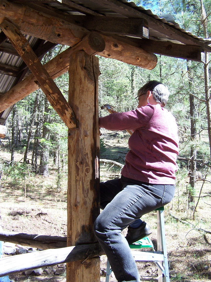 Shorty scraping hard to remove bark from a post in the Medina Unit Kitchen.
