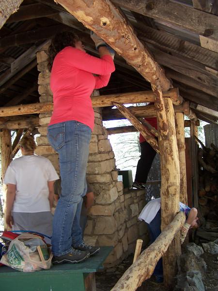 Dauber scraping a beam at the Medina Unit Kitchen.