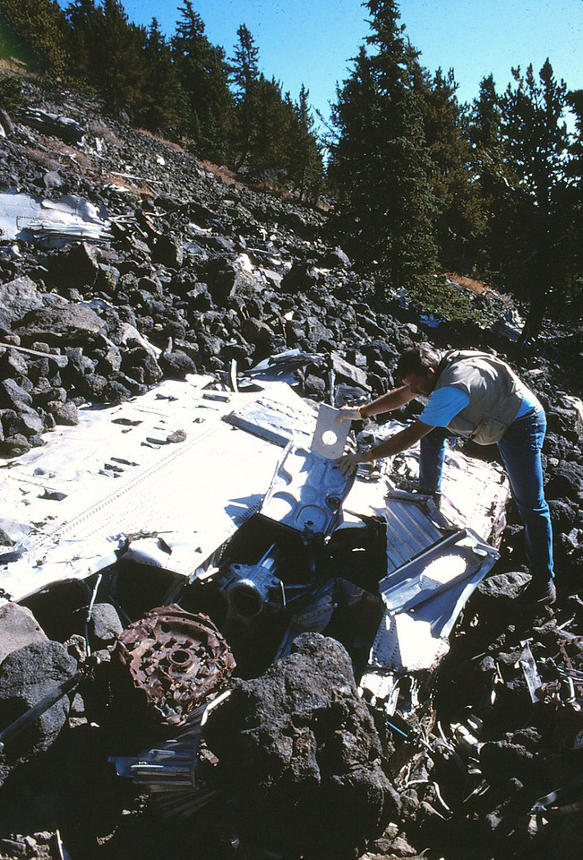 Scott Featherstone seen here examining a part of the lower left-side wing structure with the retracted main landing gear and wheel assembly. (1991)