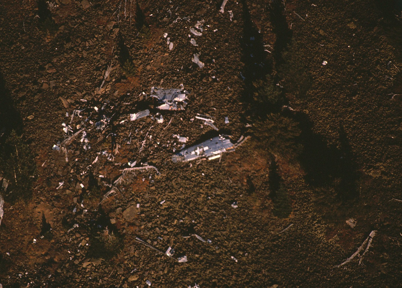 THE CRASH SITE - APRIL 1991<br /> <br /> This aerial photo taken before my initial hike to the crash site shows a trail of wreckage debris and a wing section with a painted star and bar insignia. (1991)
