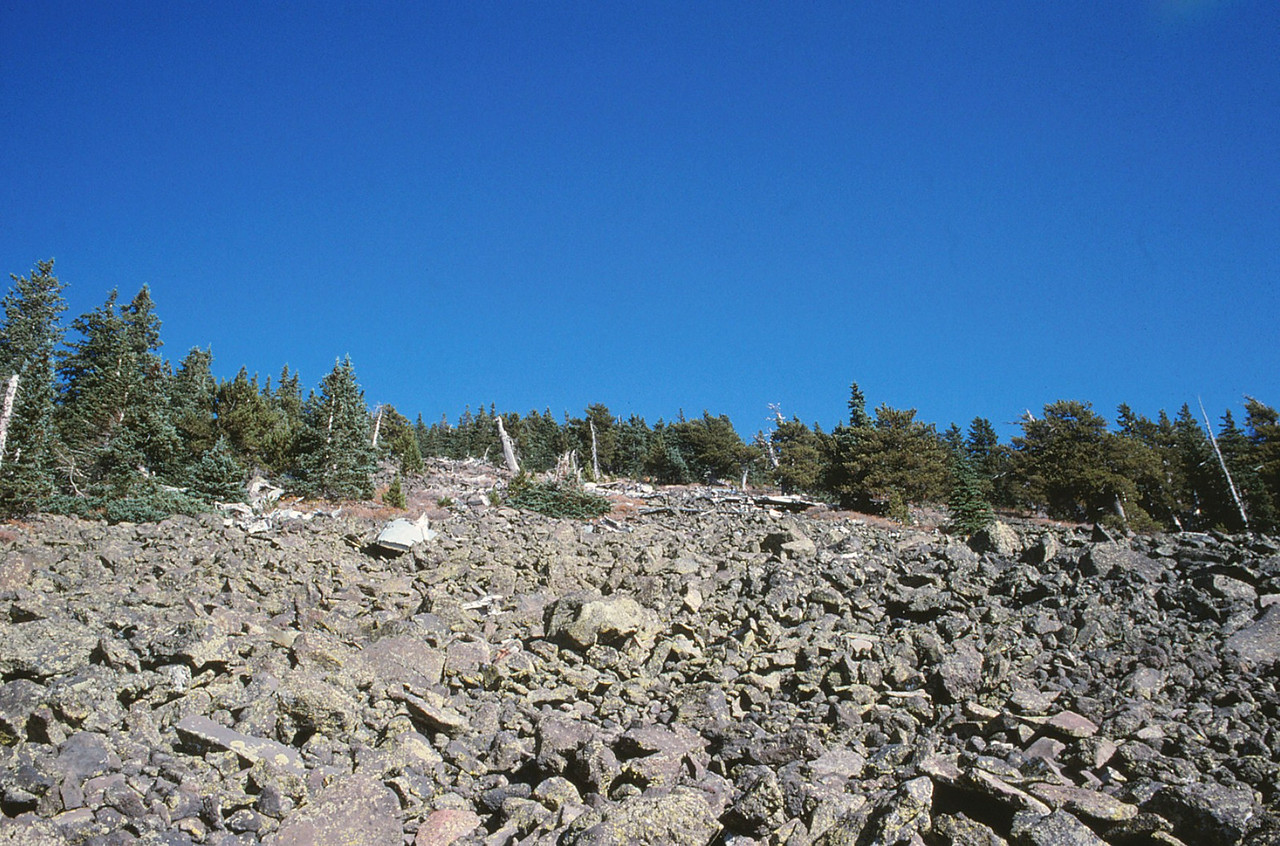 Looking up at the talus slope, wreckage can be be seen in the distance.