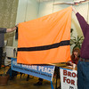 """Artur Lipori of <a href=""""http://www.refugeenation.org/"""" target=""""blank""""><b>Refugee Nation</b></a> displays a flag that his group has designed to show solidarity and understanding of the plight of refugees. It is orange to recall the color of life preservers as people flee their homeland,often via  treacherous journeys across dangerous open water."""