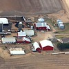 An Eastern Iowa farm with red buildings and white roofs.