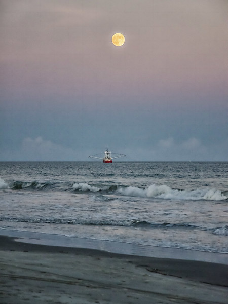 Shrimp boat out of Cherry Point on Wadlamaw Island, SC fishing off the Kiawah Island beach as the moon rises on the horizon.