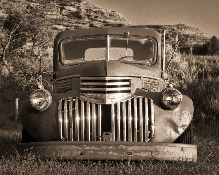 A 70-year old Farm truck is missing one of it's teeth from its chrome grill.  The truck is still used occasionally on the ranch in the heart of the North Dakota Badlands.