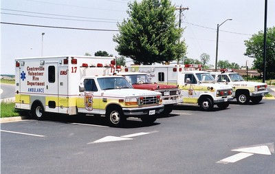 A group of apparatus at Centreville waiting to be sold in 2003, L-R:  -Medic 417, a 1996 Ford F-350/Medic Master (Shop #V092)  -Brush 417, a 1979 Ford F/Moryville (Shop #V096)  -Reserve Medic unit, a 1984 Ford E-350/First Responder (Shop #V093)  -Car 17, a 1986 Chevy Suburban (Shop #V097).
