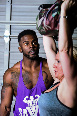 William Savoy guides Chrystal Ragains as she raises a weighted bag over her head at Savoy Fitness in Clarksville. Staff photo by Tyler Stewart