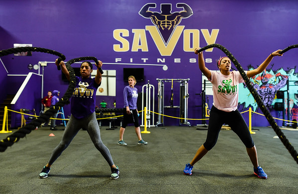 Elle Smith, and Meagan Shaver, both of Louisville, work through a battlerope exercise station as part of the boot camp program at Savoy Fitness in Clarksville. Staff photo by Tyler Stewart