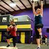 Lori Woodward, Sellersburg, and Anne Keller, Jeffersonville, work through weighted step-ups at Savoy Fitness. Staff photo by Tyler Stewart