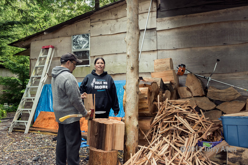 Cetacea lab staff chopping up cedar for kindling, Gill Island, mid-coast British Columbia