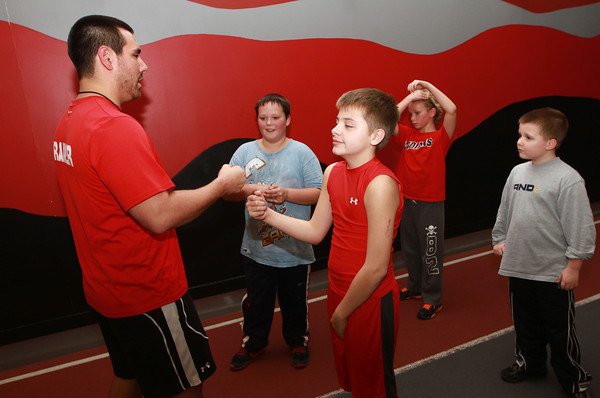 11-28-12<br /> Parisi Speed School at Club Fitness 24<br /> Instructor Andrew Dulmes fist bumps 12-year-old Reis Coy after Coy correctly answered a question.<br /> KT photo | Kelly Lafferty
