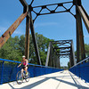 7-23-13<br /> Nickel Plate trail<br /> A woman bikes on the Nickel Plate trail across the Wabash River from Peru.<br /> KT photo | Kelly Lafferty