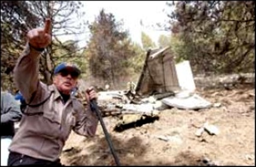 THE CRASH SITE - JANUARY 2003<br /> <br /> Coconino County Sheriff Joe Richards stands at the crash site and points to the path that the plane took as it crashed into Schultz Peak.<br /> (Arizona Daily Sun)