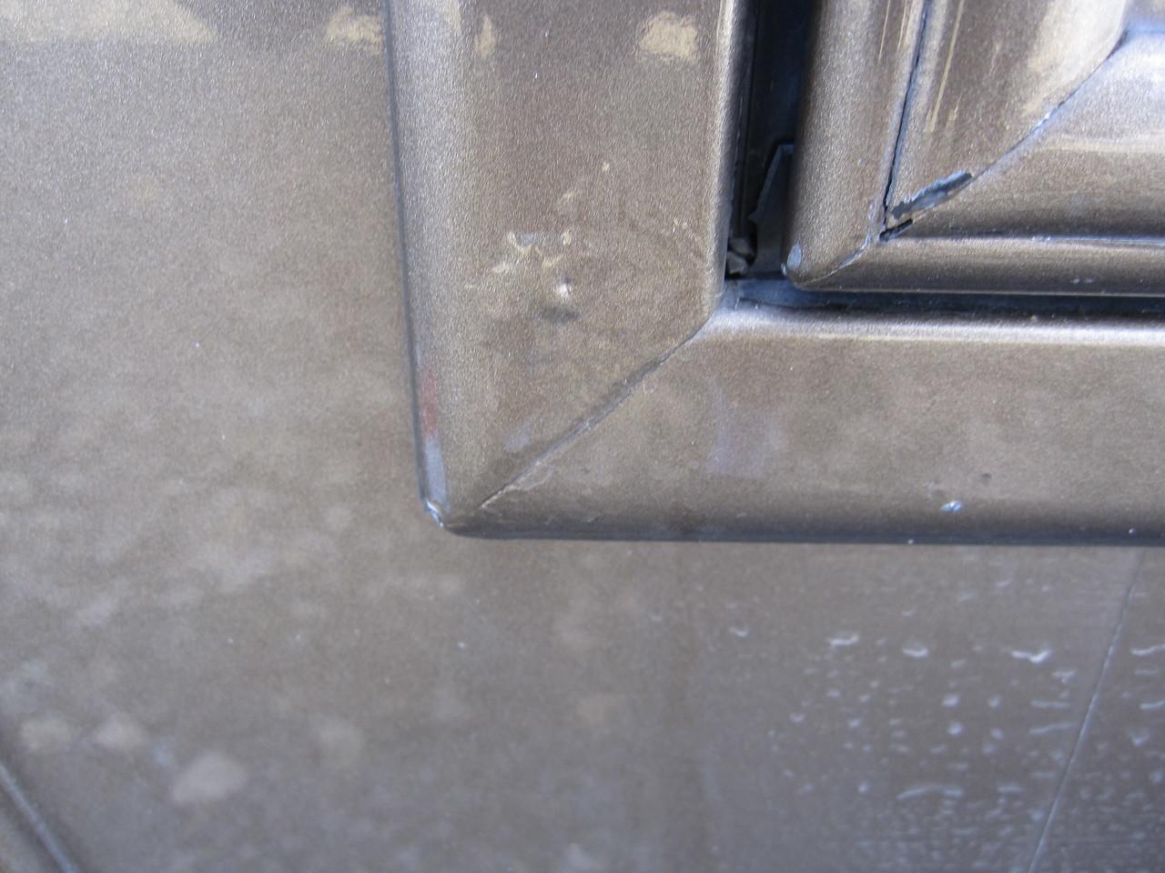 Paint blistering primarily on aluminum trim surfaces.