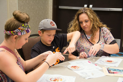 Jessica Anderson and her children Turtle and Hunter Anderson, all from Snyder, learn to make beaded jewelry.