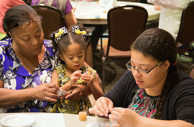 Left to right, Mary Watson, Pam Watson and Diwala Gibson, three generations of women, sit down to make beaded jewelry.