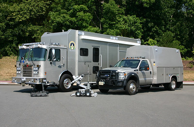 A group photograph of Bomb Disposal 600 and Bomb Disposal 660, with two of the Fire Marshal's remote control robots.    This photograph was taken in July of 2012 near the apparatus warehouse in Ashburn.