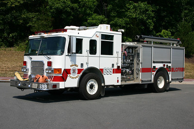 Reserve Engine 699 has made its mark across the county.  Originally delivered as the first new Training Center fire engine, this 2002 Pierce Enforcer 1250/750 originally had a see through pump panel so students could see the plumbing behind the pump panel.  After the Training Center, the Pierce was in service in Neersville as Engine 16.  At that time, the pump panel was changed out to a regular one.  From Engine 16 it became a county reserve engine.  This 2002 Pierce was also the first Engine 623 when the county took over operations at Station 23 in Ashburn.  When Station 23 received their new Pierce, the 2002 model became Engine 699 and is kept at the Ashburn warehouse when not being used.  This photograph was taken in July of 2012 at the county warehouse in Ashburn.