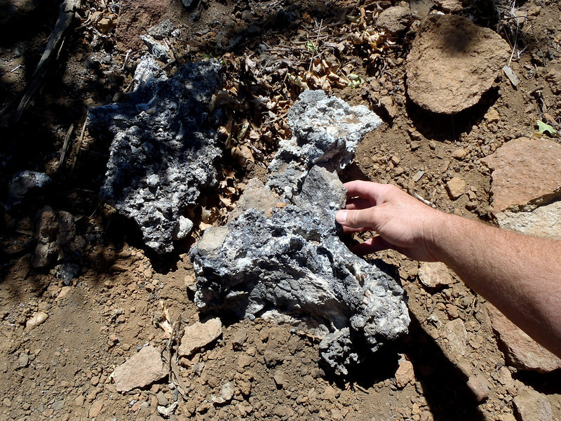 These clumps of aircraft aluminum slag identify the main impact site of the B-17F. They were located near a concentrated burn area marking the location where the aircraft came to rest.