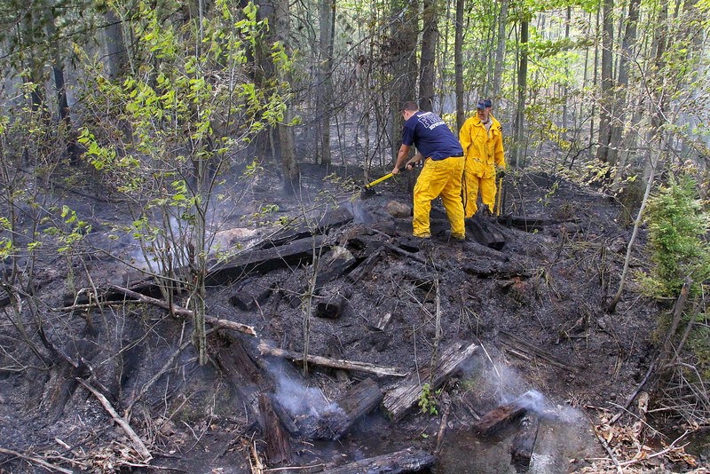 Gardner firefighters Matt Berner and Jeff Sudnes, in all yellow, help fight a brush fire that broke out near the train tracks off of Murray Road in Ashburnham on Tuesday afternoon. SENTINEL & ENTERPRISE/JOHN LOVE