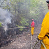 Gardner Fire Capt. Richard Ares helps Gardner Firefighter/EMT Mark Bettez fight a brush fire that broke out near the train tracks off of Murray Road in Ashburnham on Tuesday afternoon. SENTINEL & ENTERPRISE/JOHN LOVE