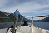 Man enjoying the splendid scenery from the bow of his boat, Mussel Inlet, mid-coast BC