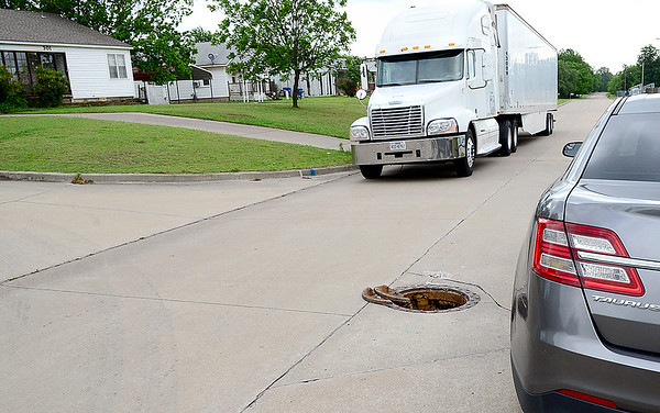 Staff photo by Kevin Harvison |<br /> Traffic passes an exposed man hole cover on Third Street and Fillmore Avenue.