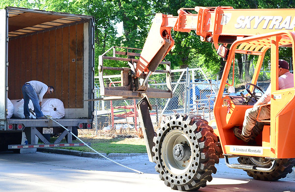 Kevin Harvison | Staff photo<br /> Workers remove new Astro Turf for Hook Eales Stadium Monday morning.