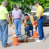 Staff photo by Kevin Harvison |<br /> City of McAlester employee measure for a new man hole cover at the intersection of Third Street and Fillmore Avenue Wednesday.