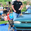 Staff photo by Kevin Harvison |<br /> Kiowa Assistant Chief and K-9 hander controls Kiowa K-9 Officer Hassan as the two work a car with drugs in it during a Kiowa police department K-9 demonstration at the Kiowa Public School.