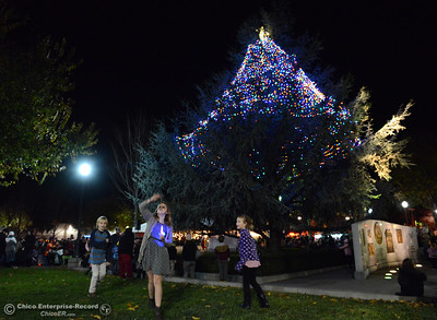 Left to right, Brenan Wright, 8, Justice Creamer, 12, and Avery Wright, 5, play in the grass at City Plaza moments after the 62-foot tall Blue Aspen is lit with 8,000 electric lights Friday, Dec. 4, 2015, at the annual Christmas Tree Lighting in Chico, California. (Dan Reidel -- Enterprise-Record)