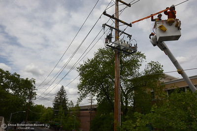 PG&E linemen Mike Plummer, left, and Brett St. Clair, right, put a safety device in place as they work on a 4,000-volt powerline Thursday, April 21, 2016, on the 100 block of Ivy Street in Chico, California. (Dan Reidel -- Enterprise-Record)